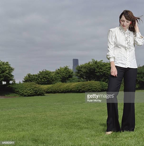 young woman standing barefoot in field, looking down - down blouse stockfoto's en -beelden