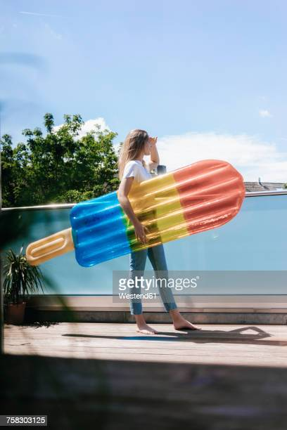 Young woman standing barefoot on balcony with an ice lolly shaped airbed