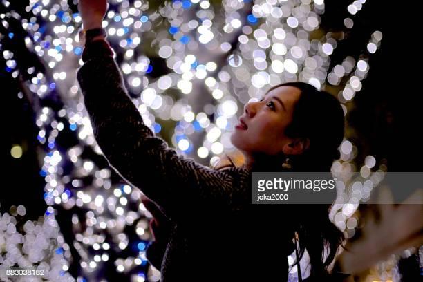 クリスマス イルミネーションの前に立っている若い女性