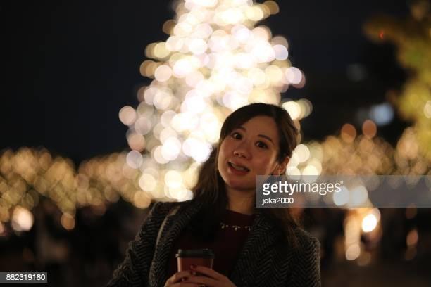 クリスマス ライトの前に立っている若い女性