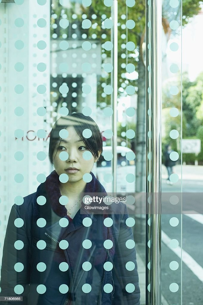 Young Woman Standing Behind A Glass Door Stock Photo Getty Images