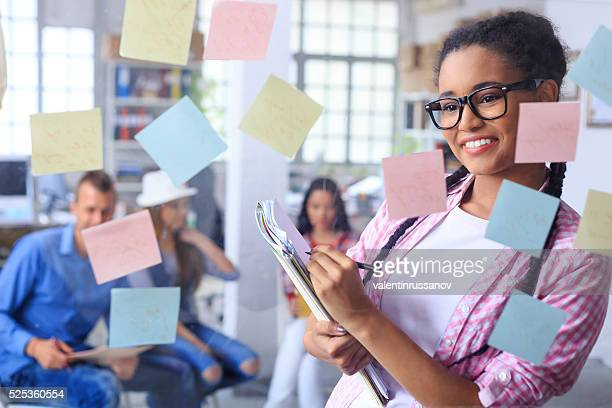 Young woman standing behind a glass wall with sticky notes