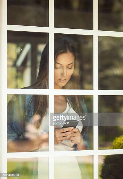 Young woman standing behind a window with phone