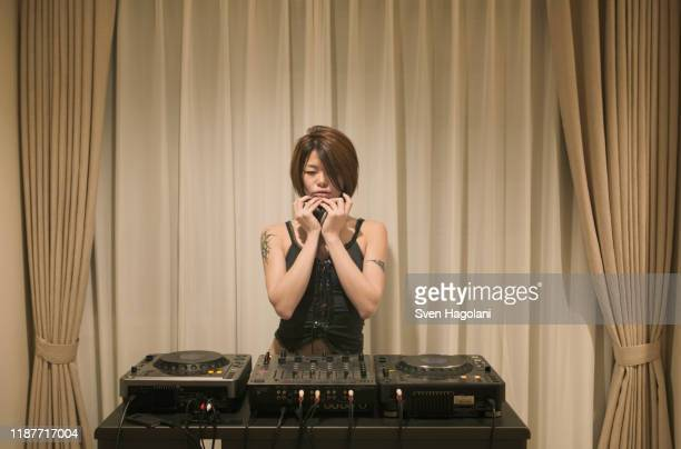 young woman standing behind turntables - クラブdj ストックフォトと画像