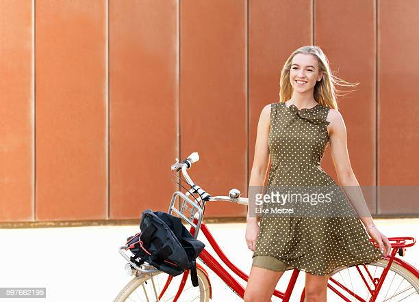 young woman standing beside bicycle - sundress stock pictures, royalty-free photos & images