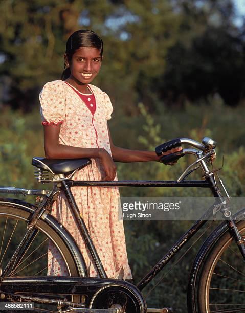 young woman standing beside bike, sri lanka - hugh sitton photos et images de collection