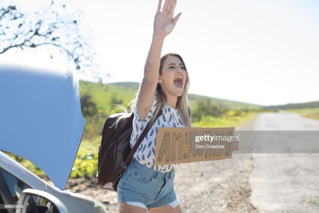 Young woman standing beside car, holding hitch-hiking sign saying anywhere, gesturing with hand : Stock-Foto