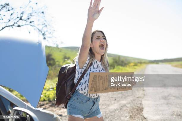Young woman standing beside car, holding hitch-hiking sign saying anywhere, gesturing with hand