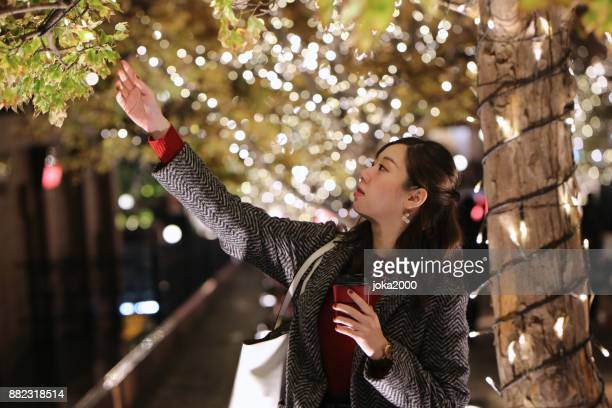 クリスマス ツリーの横に立っている若い女性