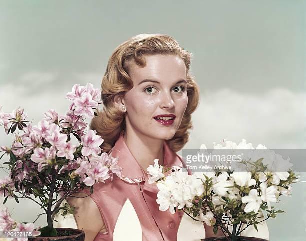 Jeune femme debout à côté de fleurs, portrait