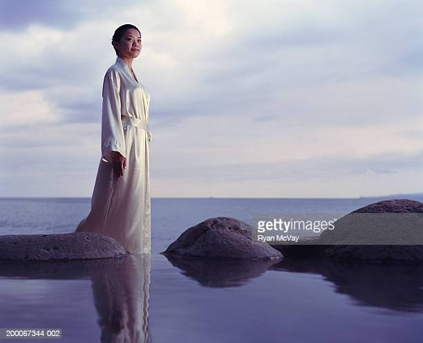 young woman standing beside hot spring, sea in background - バスローブ ストックフォトと画像
