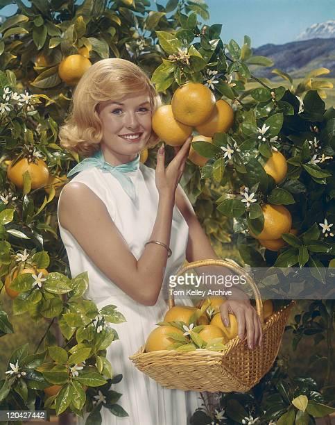 Young woman standing beside orange tree holding orange basket, smiling, portrait