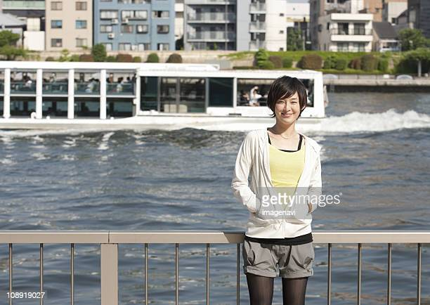 Young woman standing beside river