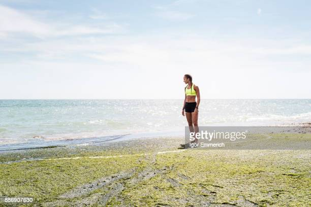 Young woman standing beside sea, looking at view