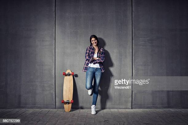 Young woman standing besides her longboard