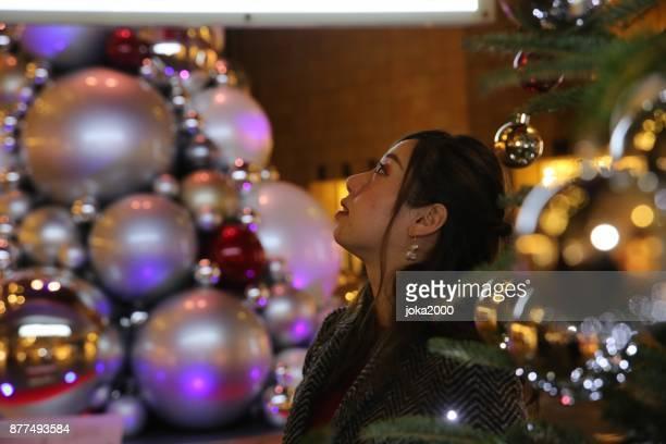 クリスマス ツリーの間に立って若い女性