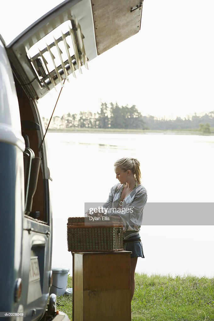 Young Woman Standing by a Motor Home Unpacking a Hamper : Stock Photo
