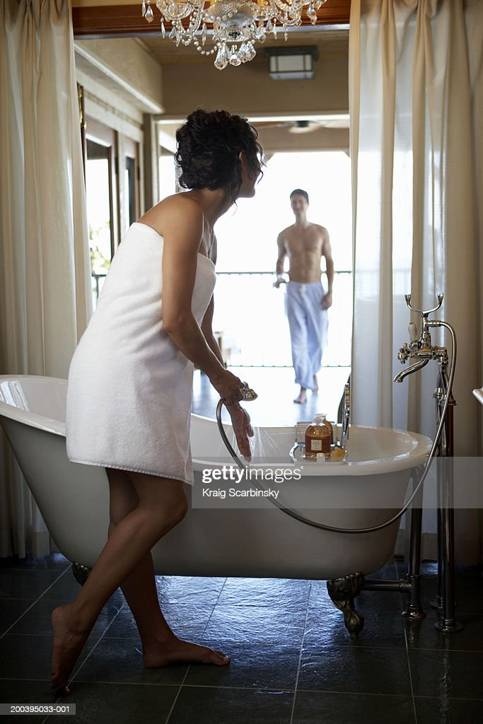 Young woman standing by bath holding shower head : Stock Photo