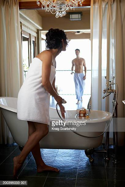 young woman standing by bath holding shower head - couples showering stock pictures, royalty-free photos & images