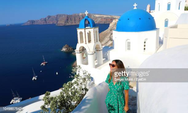 young woman standing by church on mountain against clear blue sky during sunny day - greece tourism stock pictures, royalty-free photos & images