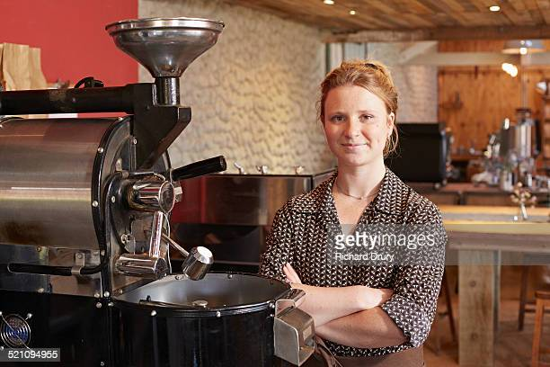 Young woman standing by coffee roaster