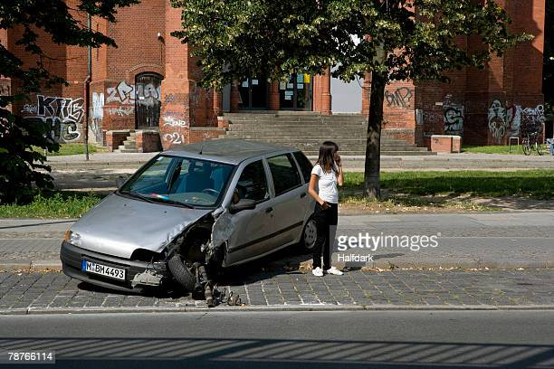 A young woman standing by damaged car