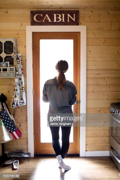 Young woman standing by doorway, looking through window