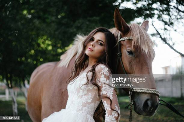 young woman standing by horse on field during sunny day - batom rosa - fotografias e filmes do acervo
