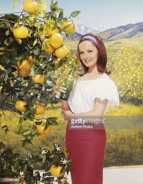 Young woman standing by lemon tree holding cold drink, smiling, portrait