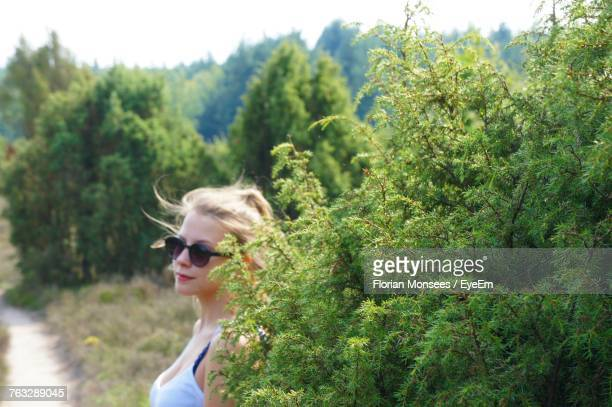Young Woman Standing By Plant