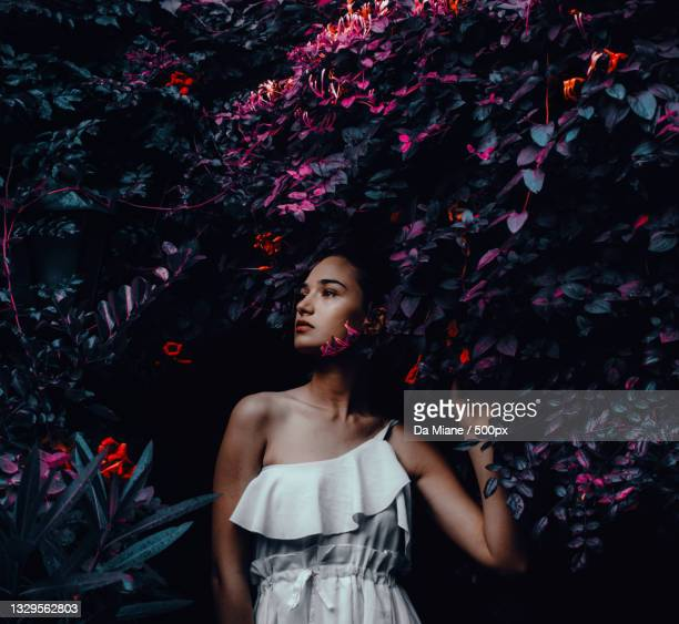 young woman standing by plants - editorial stock pictures, royalty-free photos & images
