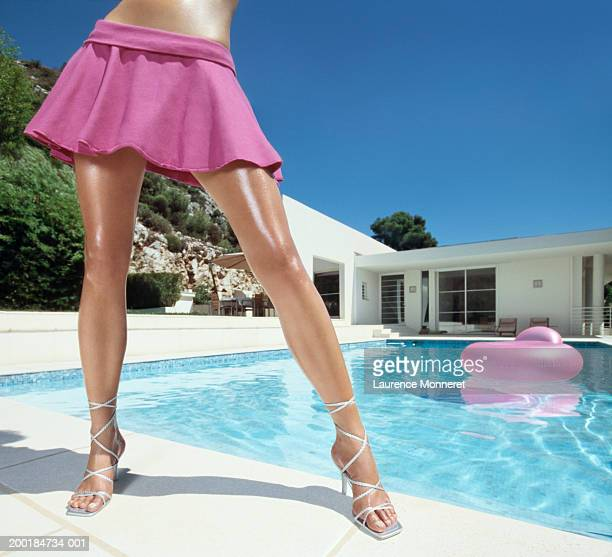 young woman standing by pool, low section - beautiful legs in high heels stock pictures, royalty-free photos & images