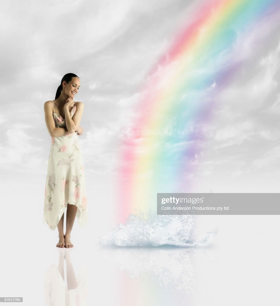 Young woman standing by rainbow's end : Bildbanksbilder