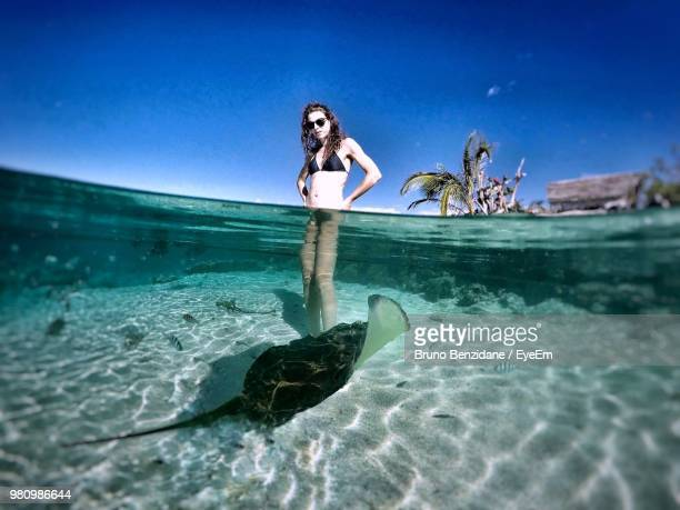 young woman standing by stingray in sea against clear blue sky - femme tahitienne photos et images de collection