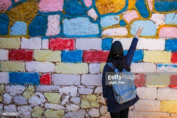 Young woman standing by the colorful wall