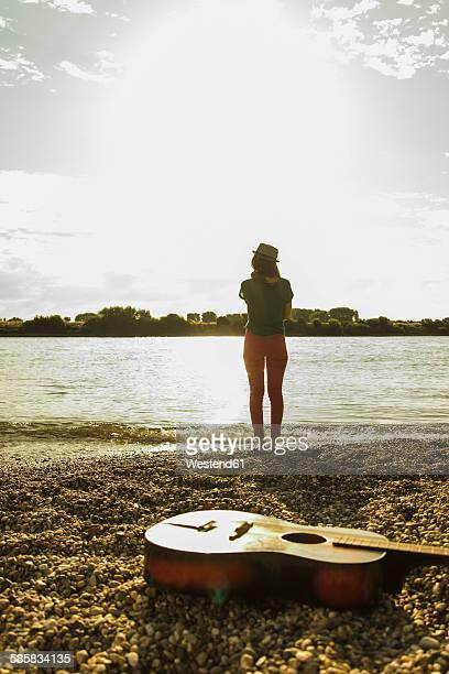 Young woman standing by the riverside with guitar in foreground