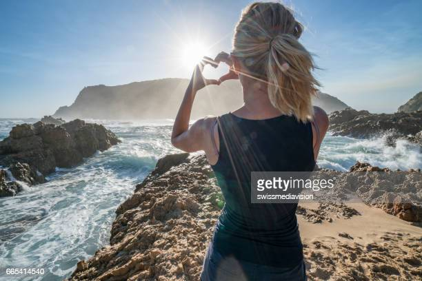Young woman standing by the sea makes heart shape frame