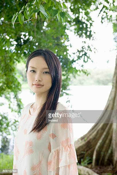 young woman standing by tree, portrait - 若い女性一人 ストックフォトと画像