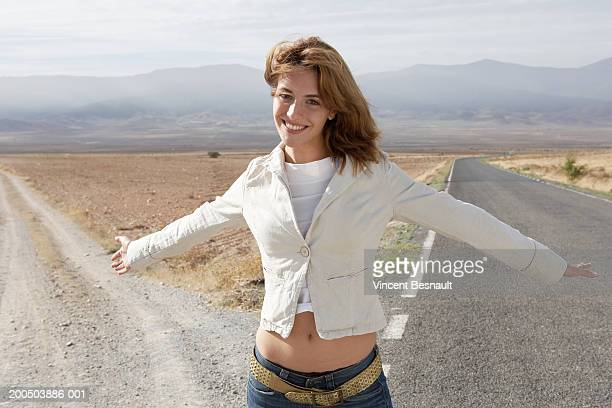young woman standing by two roads, arms outstretched, portrait - human arm stock pictures, royalty-free photos & images