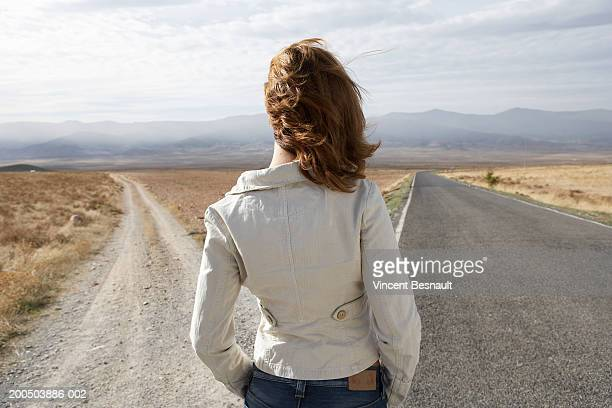 young woman standing by two roads, outdoors, rear view - forked road stock pictures, royalty-free photos & images