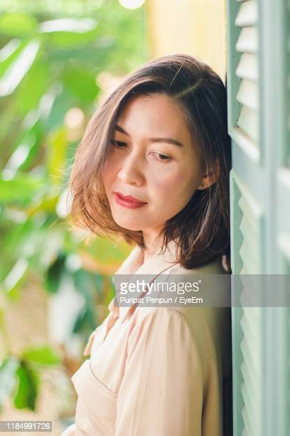 young woman standing by wall - thai mueang photos et images de collection