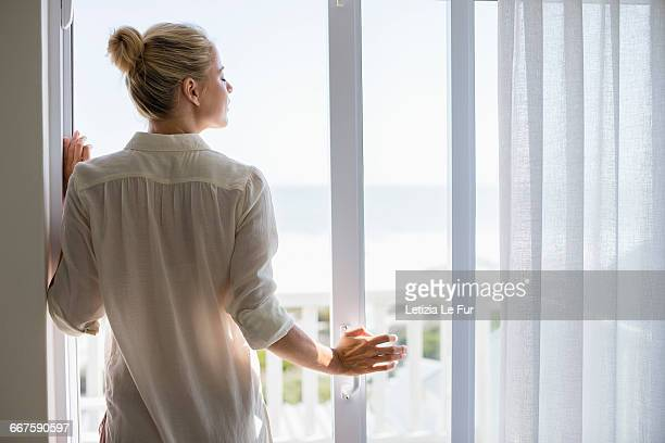 young woman standing by window at home - erker stockfoto's en -beelden