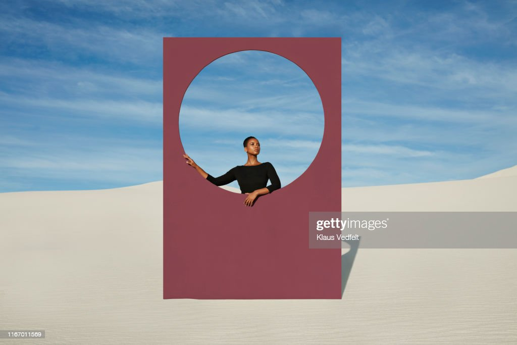 Young woman standing by window frame at white desert : ストックフォト