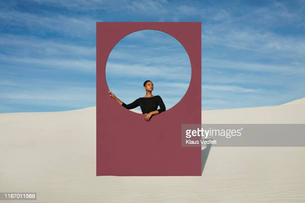 Young woman standing by window frame at white desert