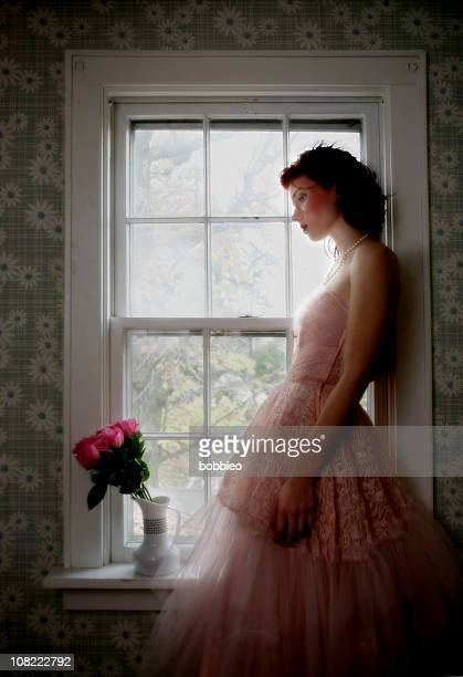 young woman standing by window wearing pink lace dress - pink dress stock pictures, royalty-free photos & images