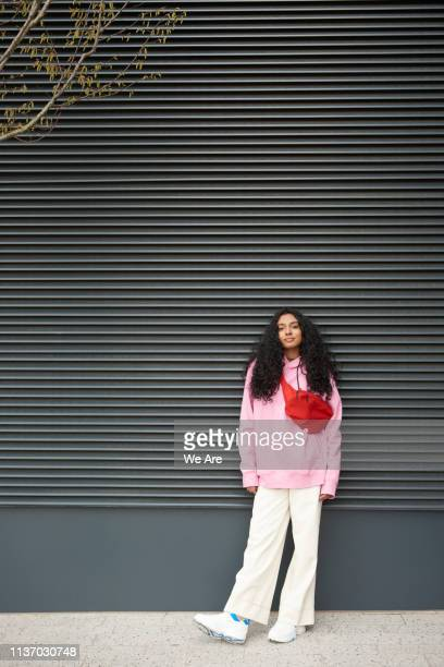 young woman standing casually against graphic background - casual clothing photos et images de collection