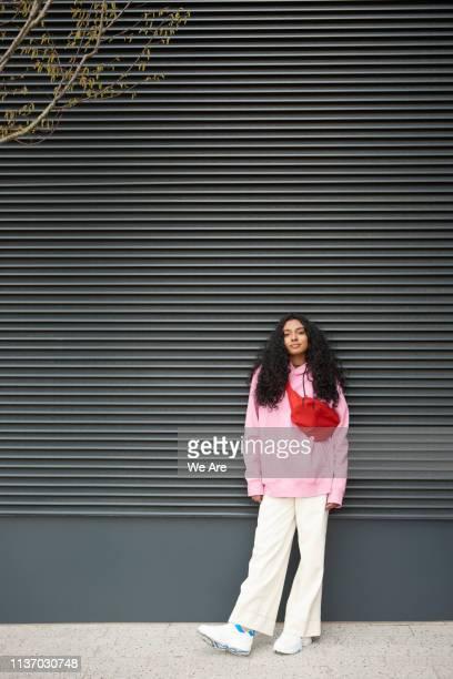 young woman standing casually against graphic background - bolsa rosa - fotografias e filmes do acervo