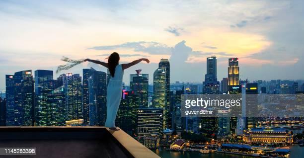 as mãos eretas da mulher nova rised no telhado do arranha-céus na cidade de singapore - membro - fotografias e filmes do acervo