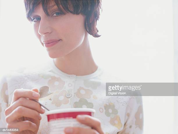 Young Woman Standing Holding an Ice Cream Container, Closeup