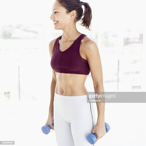 young woman standing holding dumbbells
